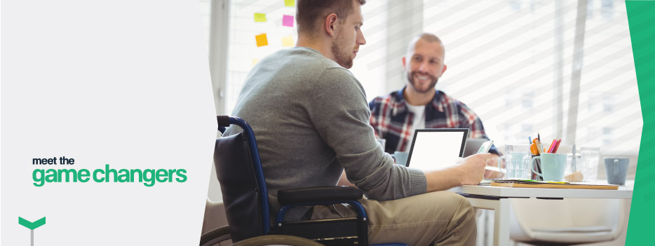 Man in wheel chair sitting at desk collaborating with a colleague